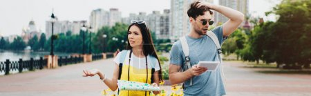 panoramic shot of handsome man holding digital tablet and asian woman holding map