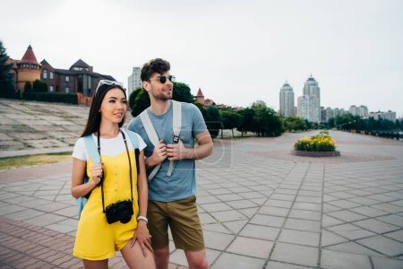 Photo for Handsome man and asian woman with backpacks looking away - Royalty Free Image