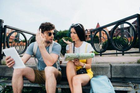 triste homme tenant tablette numérique et asiatique femme tenant carte