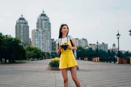 Photo pour Souriant et asiatique femme tenant appareil photo numérique et regardant loin - image libre de droit