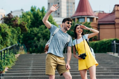 Photo for Handsome man and asian woman with backpacks waving and looking away - Royalty Free Image