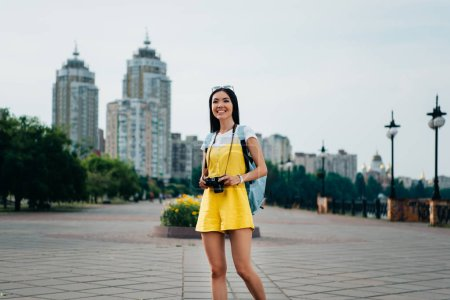 attractive and asian woman in overalls holding digital camera