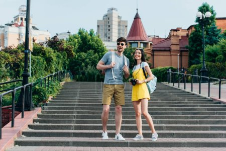 handsome man and asian woman smiling and looking away