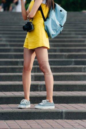Photo pour Vue recadrée de la femme en salopette avec appareil photo numérique - image libre de droit