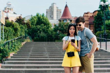 Photo pour Sourire et beau homme et asiatique femme regardant smartphone - image libre de droit