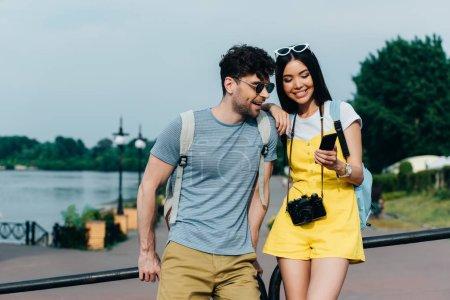 Photo pour Beau homme et femme asiatique souriant et regardant le smartphone - image libre de droit