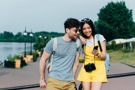 handsome man and asian woman smiling and looking at smartphone