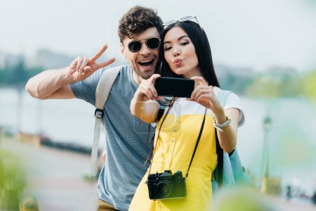 Photo for Handsome man showing peace sign and asian woman taking selfie - Royalty Free Image