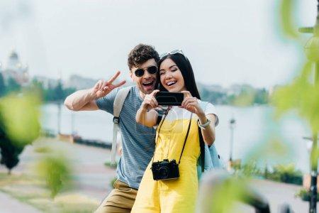 Photo pour Bel homme affichant le signe de paix et la femme asiatique prenant le selfie - image libre de droit