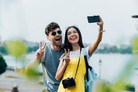 Photo pour Handsome man and asian woman showing peace signs and taking selfie - image libre de droit