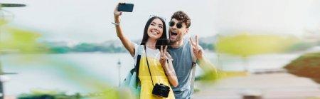 Foto de Panoramic shot of handsome man and asian woman showing peace signs and taking selfie - Imagen libre de derechos