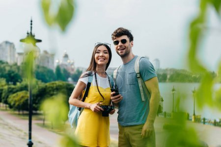 Photo for Handsome man and asian woman smiling and looking away - Royalty Free Image
