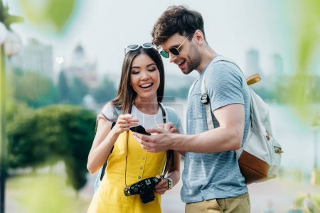 Photo for Handsome man and asian woman smiling and looking at smartphone - Royalty Free Image