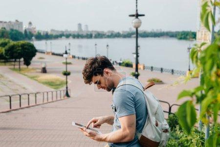 Photo pour Bel homme dans des lunettes avec sac à dos en utilisant une tablette numérique - image libre de droit