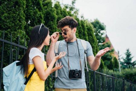 Photo pour Choqué homme et asiatique femme parler et regarder l 'autre - image libre de droit