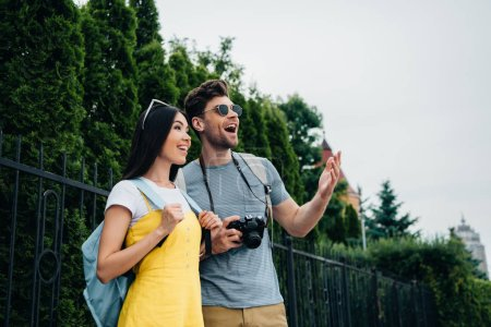 Photo for Shocked man and asian woman with backpacks looking away - Royalty Free Image