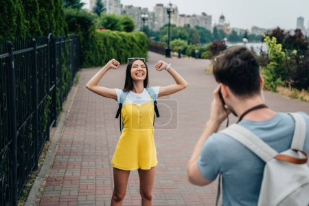 Photo for Man taking photo and asian woman showing yes gesture - Royalty Free Image