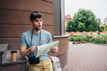 Photo for Thoughtful and handsome man in glasses holding map and looking away - Royalty Free Image