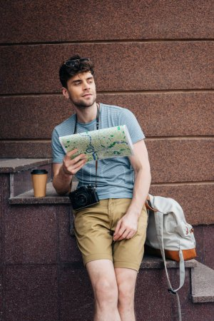 Photo pour Handsome man in glasses holding map and looking away - image libre de droit