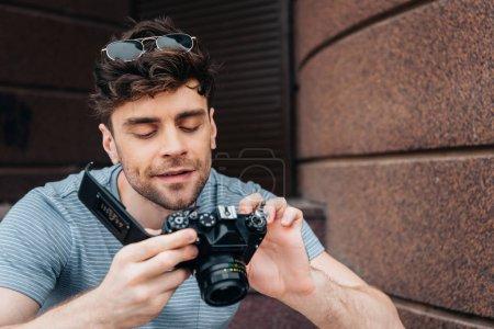 Photo pour Bel homme en lunettes regardant l'appareil photo numérique à l'extérieur - image libre de droit