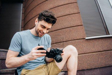 Photo pour Homme souriant et beau dans des lunettes regardant appareil photo numérique - image libre de droit