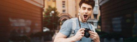 Photo pour Photo panoramique de bel homme en t-shirt tenant appareil photo numérique et regardant l'appareil photo - image libre de droit