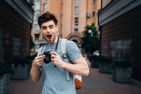 handsome man in t-shirt holding digital camera and looking at camera