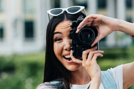 Photo for Attractive and asian woman with glasses smiling and taking photo - Royalty Free Image