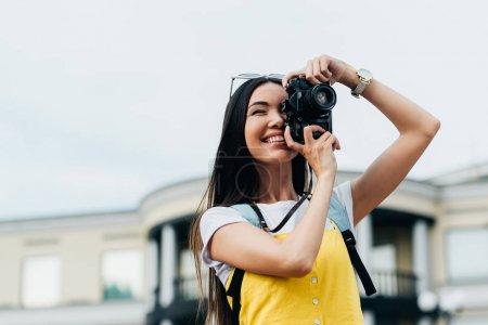 Photo pour Attrayant et asiatique femme avec des lunettes souriant et prendre des photos - image libre de droit
