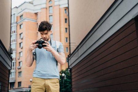 Photo pour Bel homme en t-shirt et short regardant appareil photo numérique - image libre de droit