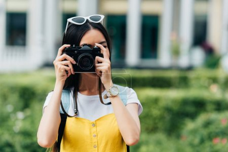 Photo for Brunette woman with glasses taking photo with help of digital camera - Royalty Free Image