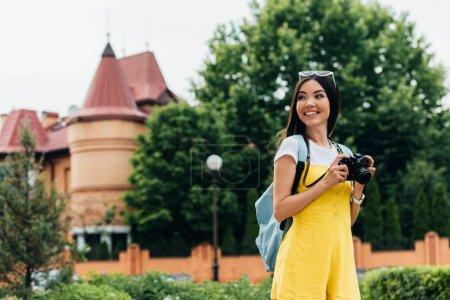 Photo pour Femme attirante et asiatique avec l'appareil-photo numérique regardant loin - image libre de droit