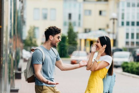 handsome man and asian woman smiling and looking at each other