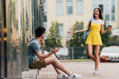 Photo pour Homme et asiatique femme souriant et tenant des tasses en papier - image libre de droit