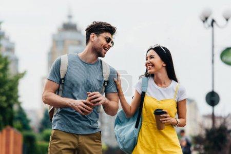 bel homme et asiatique femme souriant et tenant des tasses en papier