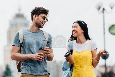 hombre guapo y mujer asiática sonriendo y sosteniendo vasos de papel