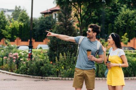 schöner Mann zeigt mit dem Finger und asiatische Frau hält Pappbecher