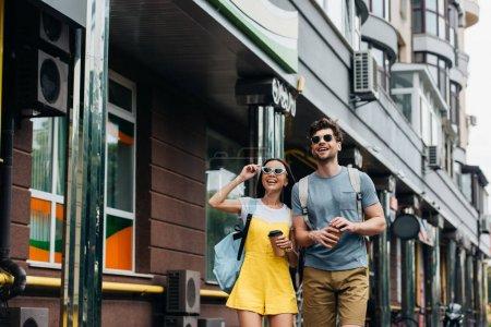 Photo pour Bel homme et asiatique femme souriant et tenant des tasses en papier - image libre de droit