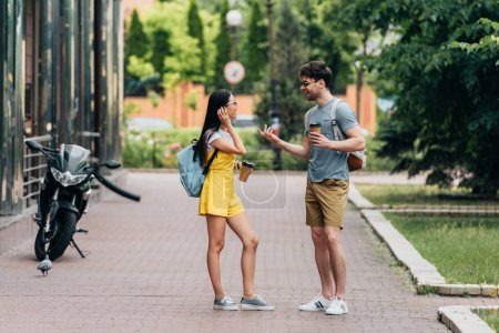 schöner Mann und Frau reden und halten Pappbecher