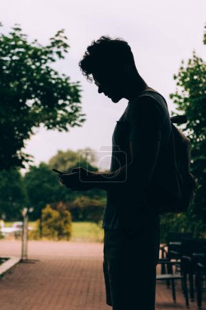 Photo for Side view of man with backpack using digital device outside - Royalty Free Image