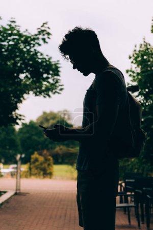 Photo pour Vue latérale de l'homme avec le sac à dos utilisant l'appareil numérique à l'extérieur - image libre de droit
