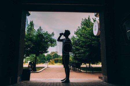 Photo pour Vue latérale de l'homme avec sac à dos boire du café de tasse en papier - image libre de droit