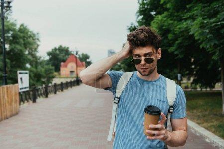 schöner Mann im T-Shirt hält Pappbecher in der Hand und schaut weg