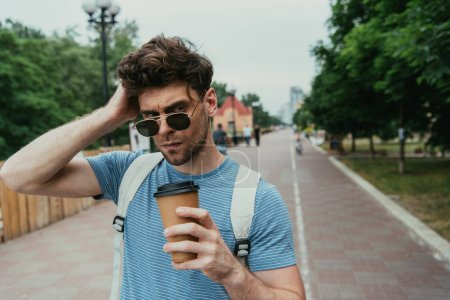 Photo for Handsome man in t-shirt holding paper cup and looking away - Royalty Free Image
