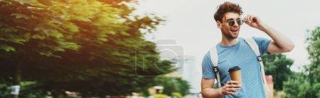 Photo pour Plan panoramique de bel homme en t-shirt tenant tasse en papier et détournant les yeux - image libre de droit