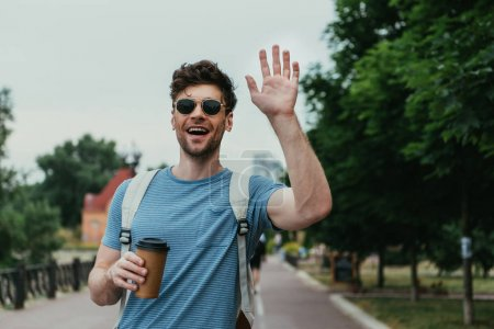 handsome man in t-shirt waving and holding paper cup