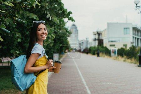 Photo pour Asiatique femme tenant tasse en papier avec café et regardant loin - image libre de droit