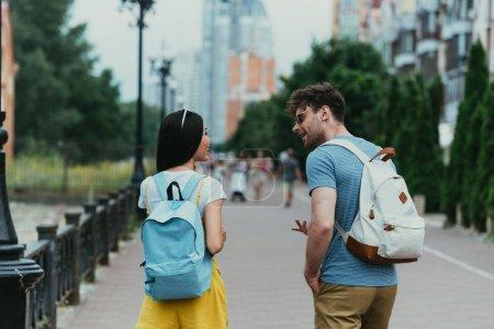 Photo pour Vue arrière de l'homme et de la femme avec des sacs à dos parlant à l'extérieur - image libre de droit