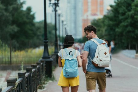 Photo for Back view of man and woman with backpacks talking outside - Royalty Free Image