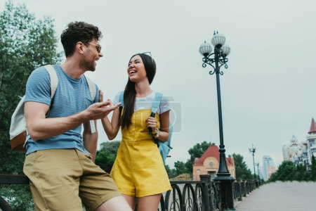Photo for Handsome man and asian woman smiling and looking at each other - Royalty Free Image